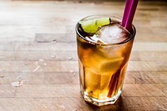 Long island iced tea cocktail with lime, ice and served with pink straw. Beverage concept royalty free stock photo
