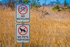 LONG ISLAND, USA, APRIL, 17, 2018: Outdoor view of informative sign of no bicycling and not pets in the area in a. Metallic structure, located at outdoors close Royalty Free Stock Images