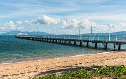 Long jetty with blue sky and clouds. Pier on tropical Magnetic Island in a blue sea with mountains in the background and cloudy sky Royalty Free Stock Photography