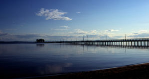 Long jetty in dusk and calm waters Stock Photos