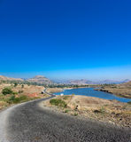 Long journey, road travel. Endless curved road. A very long journey or road trip drive. Clear blue warm summer sky and mountains scenery with a lake. A metaphor Royalty Free Stock Photo