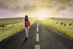 Long journey for success. Female college student walk on the road to start her journey and gain bright future royalty free stock photos