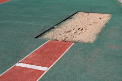 Long jump pit. Long jump sand box in athletic stadium Royalty Free Stock Photos