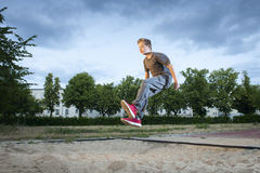 Long jumpin in the sand. Frozen shot full body shot of young male teenager jumping into a long jump pit Stock Photo