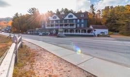 Long Lake, NY, Adirondacks, October 9, 2018: Adirondack Hotel at Sunrise in the fall. With sunburst stock image