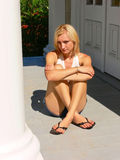 Long leg lady sitting. An young pretty lady sitting on the entrance of a house in short shorts Royalty Free Stock Images
