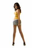 Long leg woman. Full body of an attractive tall brunette woman with long sexy legs wearing shorts and yellow tank top looking back over shoulder standing on Royalty Free Stock Image