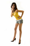 Long leg woman. Full body of an attractive tall brunette woman with long sexy legs wearing shorts and yellow tank top bending while standing on white background Stock Photography