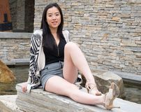 Long legged Asian girl sits by water feature. A lovely model sits on a stone wall by a water feature as her long legs stretch to the camera position stock photos