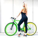 Long-legged beautiful blond girl in black sexy outfit and sneakers posing against a gray wall in the summer afternoon Royalty Free Stock Images