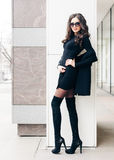 Long-legged beauty of a brunette in sunglasses posing. A small black outfit, high boots with high heels. Fashion. Style. Stock Image