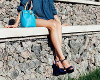 The long-legged beauty rests on stone steps on a hot summer day in a denim outfit, blue incredible high-heeled shoes and a super-t Royalty Free Stock Photography