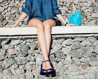 The long-legged beauty sits on stone steps on a hot summer day in a denim outfit, incredible high-heeled shoes and a super-trendy Stock Images