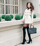 Long-legged brunette girl with long hair, dressed in a raincoat, high black high-heeled boots with a handbag posing near. A boutique in the European city stock images