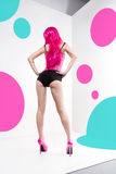 Long-legged dancer in a pink wig and high heels. White background, pink and cyan circles Stock Photos