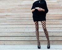 A long-legged girl in fashionable pantyhose, a black dress and black high-heeled shoes posing in the summer on wooden steps. Fashi Royalty Free Stock Image