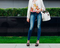 Long-legged girl in jeans and a fashionable colored blouse with a fashionable white hand bag waiting on the street for a Stock Image