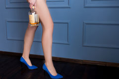 Long legged woman in blue shoes holds a nearly empty bottle of whiskey Stock Photos