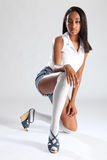 Long legs african american sexy model in shorts. Long legged young african american fashion model wearing white shirt and blue denim shorts. Woman has knee high Royalty Free Stock Images