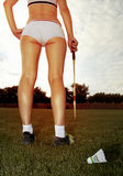 Long legs of badminton player. Long legs of woman who plays badminton on grass Stock Image