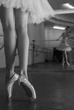 Long legs of ballerina in toeshoe. Ballerina in pointe shoes and tutu standing on toes at the bench. Reflection in the mirror in the ballet class. Classical Stock Image