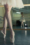 Long legs of ballerina in toeshoe. Ballerina in pointes and a pack warms up before the dance lesson. Crossed long slender female feet. Classical ballet. Prima Royalty Free Stock Photo