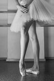 Long legs of ballerina in toeshoe. Ballerina in pointes and a pack warms up before the dance lesson. Long slender female feet. Classical ballet. Prima ballerina Stock Photos
