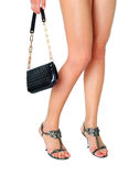 Long legs on high heels. And black purse Stock Photography