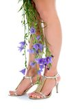 Long legs on high heels with flowers. On white Royalty Free Stock Photography