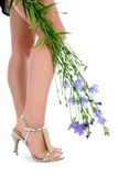 Long legs on high heels with flowers. On white Stock Photos