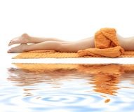 Long Legs Of Relaxed Lady With Orange Towel On Whi Royalty Free Stock Photos