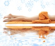 Long legs of relaxed lady with orange towel Stock Photos
