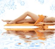 Long legs of relaxed lady with orange towel Stock Photo
