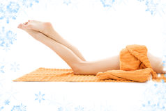 Long legs of relaxed lady with orange towel Royalty Free Stock Images
