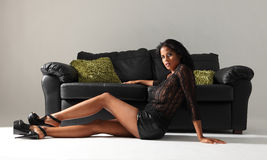 Long legs sexy african american woman and settee Royalty Free Stock Image