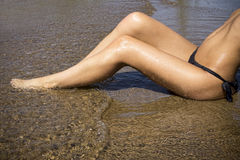 Long legs of a woman on the beach Stock Image