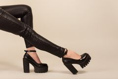 Long legs in skinny leather pants and high heels. Studio shot on white background Stock Photography