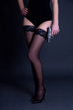 Long legs in stockings of sexy woman in black lingerie with gun Stock Photo
