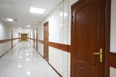 Long light hallway with wooden doors Royalty Free Stock Photo