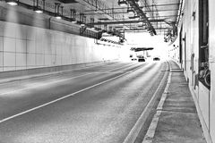 Long lightened tunnel for vehicles. B&W. Long lightened tunnel for vehicles. Black and white photogrphy stock images