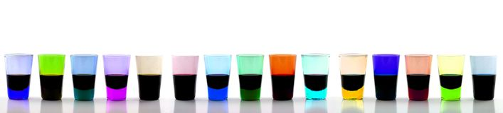 Long Line of Drinking Glasses. Close up of  a long line of 15 brightly colored drinking glasses Royalty Free Stock Images