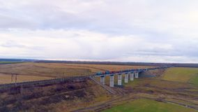 A long line of intermodal containers crosses a railway bridge. A zooming out view on a freight train with shipping containers passing a bridge stock footage