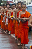 A long line of monks receiving rice offering from. NAN,THAILAND-MAY 26:A long line of monks receiving rice offering from people at Nan City of Nan Province stock images