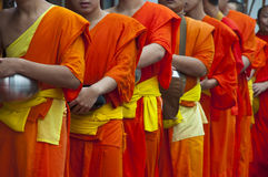 A long line of monks receiving rice offering from. NAN,THAILAND-MAY 26:A long line of monks receiving rice offering from people at Nan City of Nan Province stock photography