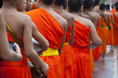 A long line of monks receiving rice offering from. NAN,THAILAND-MAY 26:A long line of monks receiving rice offering from people at Nan City of Nan Province royalty free stock images