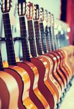 Long line of new acoustic guitars in store. Long line of new acoustic guitars in music shop Royalty Free Stock Images
