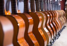 Long line of new acoustic guitars in store. Long row of new acoustic guitars in music chop Stock Photography