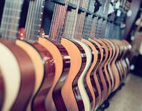 Long line of new acoustic guitars in store. Long line of new wood acoustic guitars in store Stock Photography