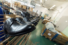 A long line of new black shiny shoes. Shoe factory, finished goods warehouse Stock Images