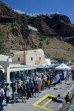 Long line of people waiting to embark on a tender to go on a cruise ship. Harbor of Santorini with a long line of people waiting to embark on a tender to go on a stock photos